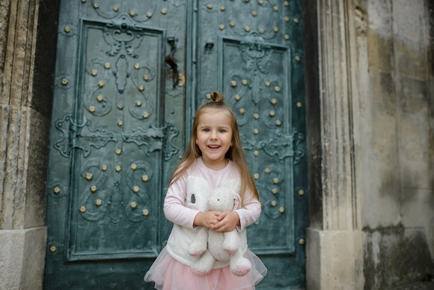 Little girl holds a toy bunny in her hands and smiles. close-up. girl posing on the background of the doors of the old church.