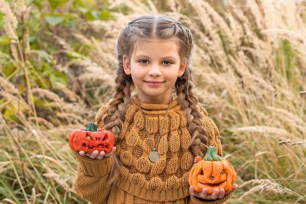 Маленькая девочка держит в руках две тыквы.