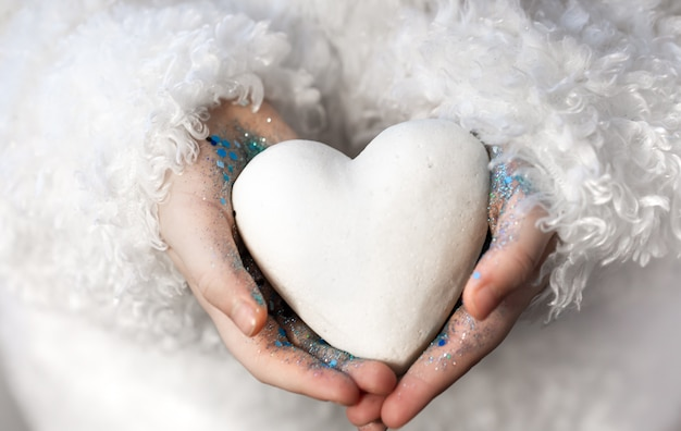A little girl holds a white heart in her hands.