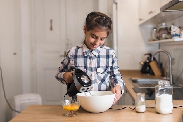 Маленькая хозяйка дома готовит на кухне, взбивая сливки миксером в миске. миксер для выпечки торта, выпечки, приготовления яблочного пирога.