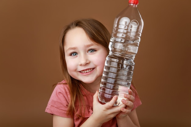 Маленькая девочка обнимает бутылку воды