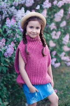 庭で大きなアジサイの茂みを抱き締める少女。春に咲くピンク、ブルー、ライラックの花