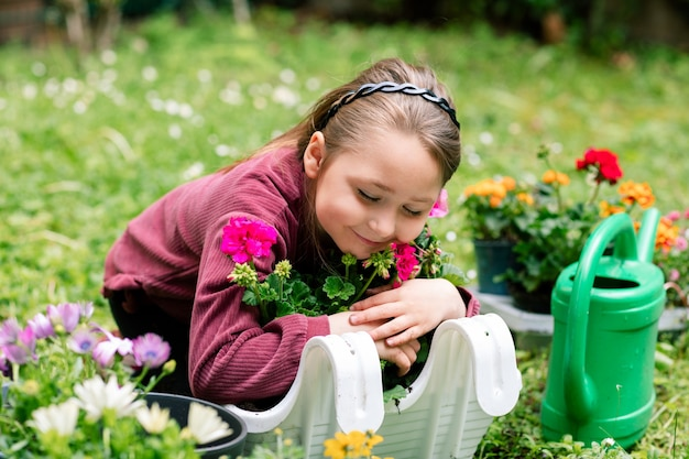 Little girl hugging geranium flowers planted in a pallet for a balcony, cautiously may cause allergies