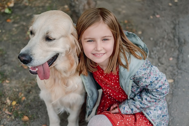 Little girl hugging golden retriever dog while looking up at camera on autumn street, top view