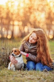 Little girl hugging her friend a dog in outdoors.