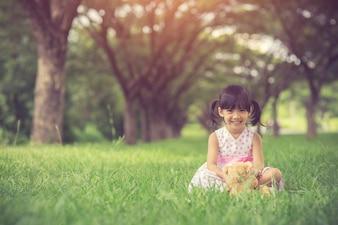 Little girl hugging her teddy bear in park.Vintage Color
