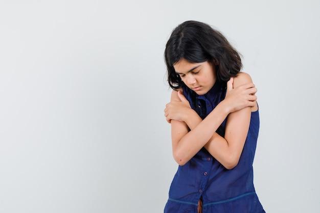 파란색 블라우스 전면보기에 눈을 감고 자신을 포옹하는 어린 소녀.