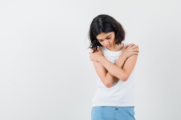 Маленькая девочка обнимает себя в белой блузке, шортах и грустно смотрит, вид спереди.