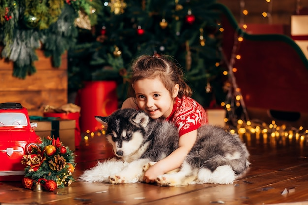 Little girl hugging a husky puppy next to a christmas tree