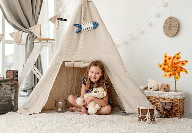 어린이 방에 wigwam에 앉아 봉제 테디를 안고있는 어린 소녀
