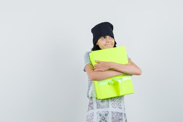 Bambina che abbraccia la casella attuale in abito da cucina e che sembra pacifica.