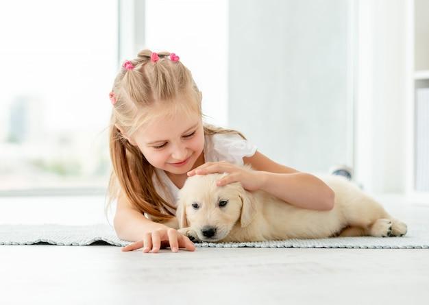 Little girl hugging retriever puppy