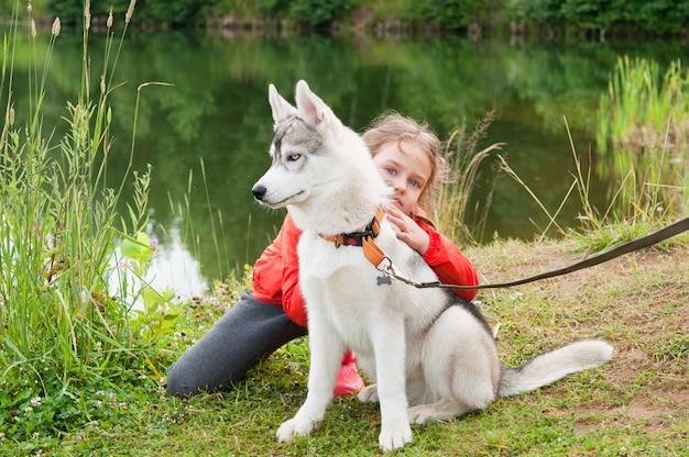 Little girl hugging siberian husky in nature
