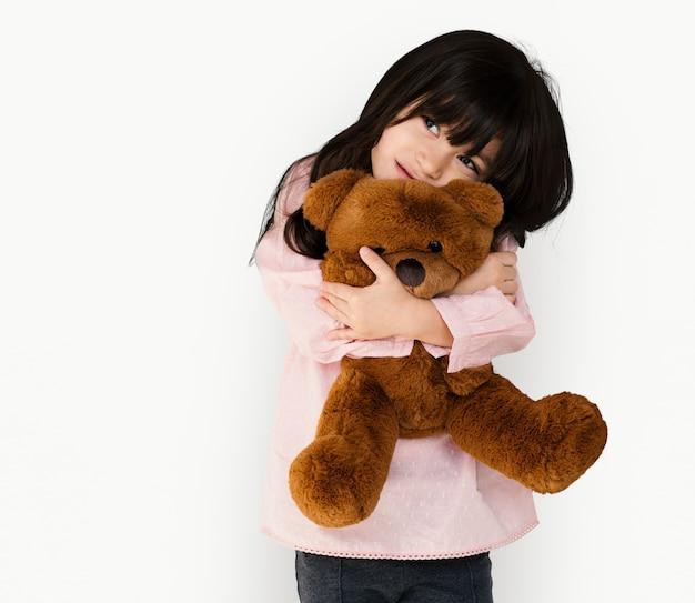 Little girl hugging teddy bear soft toy
