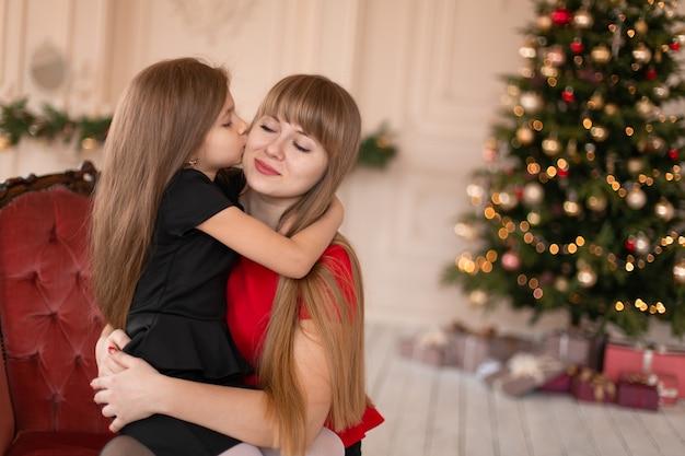 Little girl hugs her mom near the christmas tree. joyful moments of a happy childhood.