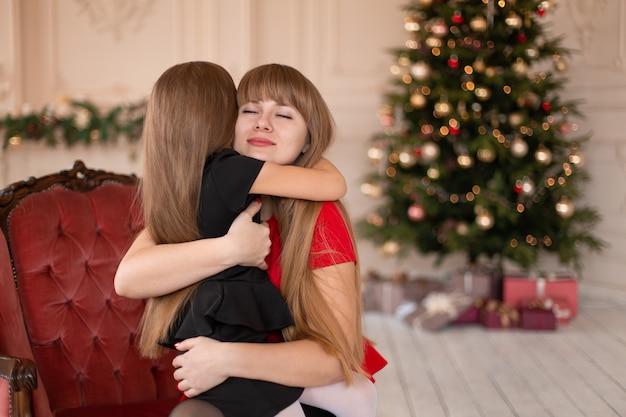 小さな女の子はクリスマスツリーの近くで彼女のお母さんを抱きしめます。幸せな子供時代の楽しい瞬間。
