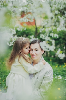 Маленькая девочка обнимает свою маму в весеннем вишневом саду