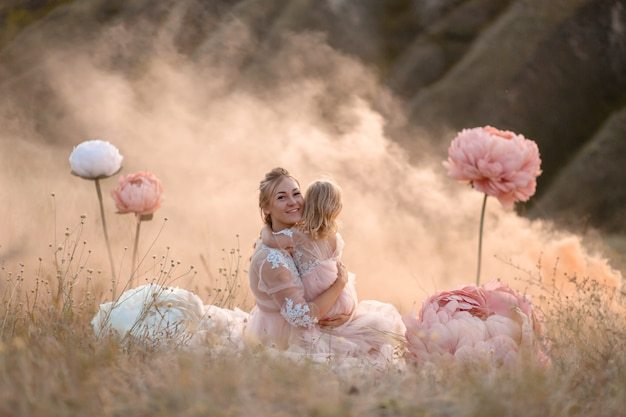 Little girl hugs mom sitting in a field surrounded by unreal big pink decorative flowers