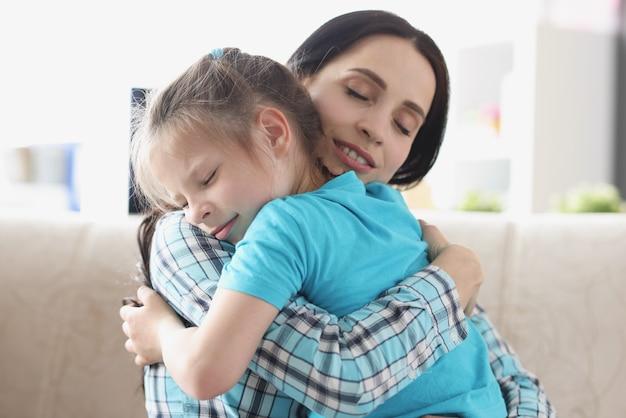 Маленькая девочка обнимает вместе со своей мамой в нежных объятиях