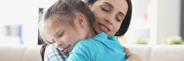 어린 소녀는 부드러운 포옹으로 어머니와 함께 포옹합니다.