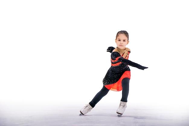 屋内アイスアリーナの美しい黒と赤のドレスアイススケートの少女アイススケーター