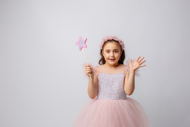Little girl in the image of a fairy with a magic wand on a white background