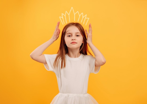 Маленькая девочка воображает себя принцессой с диадемой и позирует изолированной на желтом фоне