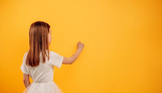 Маленькая девочка имитирует письмо на столе, изолированном на желтом фоне