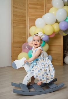 Маленькая девочка в бинтовом платье скачет на деревянной лошади по стене с воздушными шарами