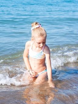 海沿いのビーチで遊ぶ水着姿の少女