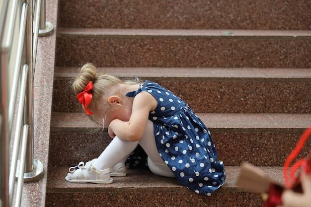 Маленькая девочка в синем платье сидит на ступеньках и плачет
