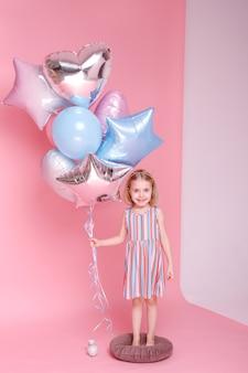 핑크 스튜디오 표면에 풍선과 함께 밝은 드레스에 어린 소녀