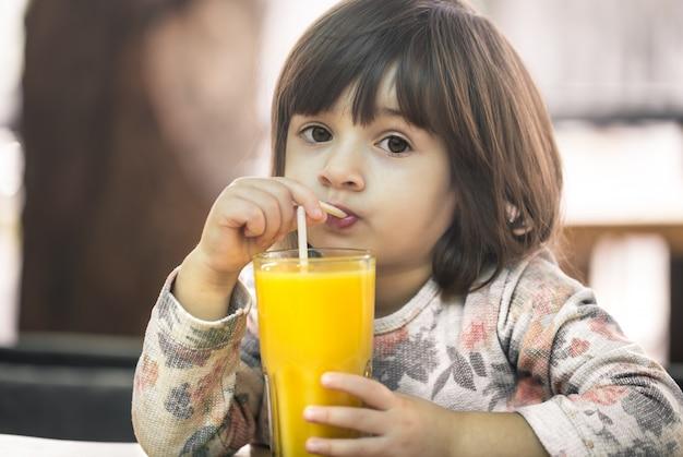Маленькая девочка в кафе пьет сок