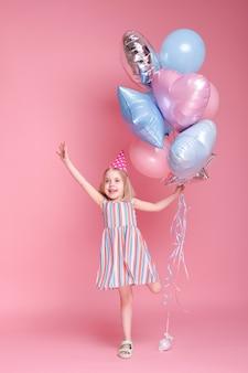분홍색 표면에 풍선과 함께 그녀의 머리에 모자에 어린 소녀