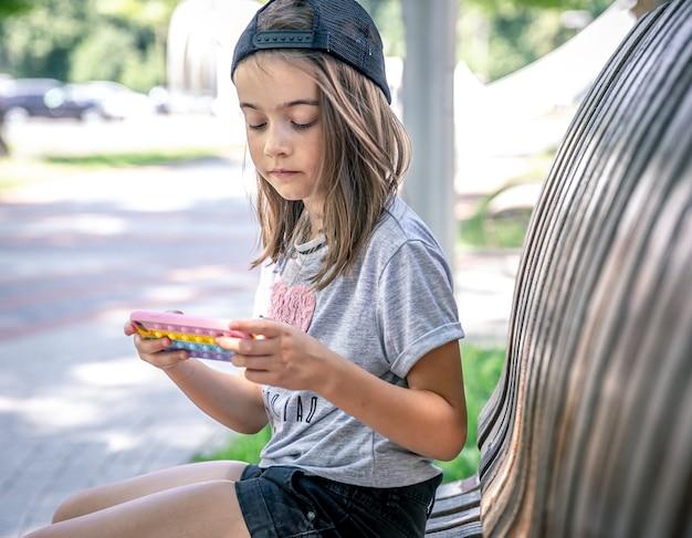 모자를 쓴 어린 소녀는 여름날 공원 벤치에 앉아 스마트폰을 사용합니다.