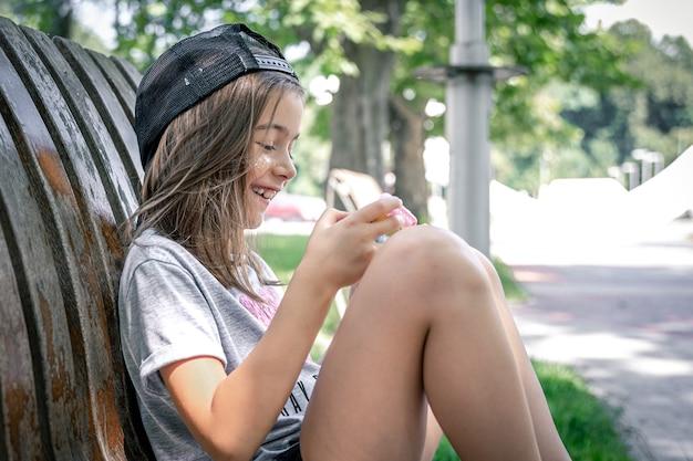 모자를 쓴 어린 소녀는 공원 벤치에 앉아 스마트폰을 사용합니다.
