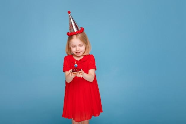 표면에 케이크와 촛불 모자에 어린 소녀