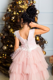 シックなピンクのドレスを着た少女がカメラに背を向けて立ち、木の下の贈り物を見る
