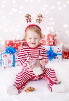 Маленькая девочка в новогоднем костюме с подарками возле елки пьет молоко и украшает оленя