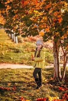 Маленькая девочка в пальто на фоне осенних деревьев в полный рост. осенний портрет