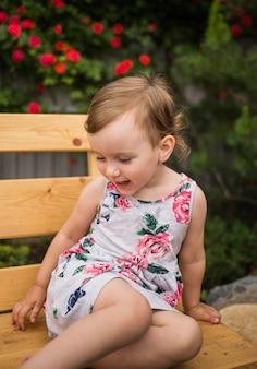 Маленькая девочка в ярком платье сидит на скамейке на фоне цветущей розы