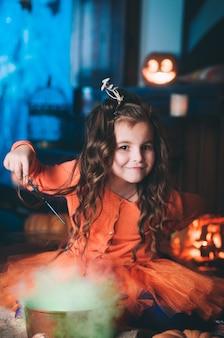 Маленькая девочка в костюме ведьмы с волшебной палочкой