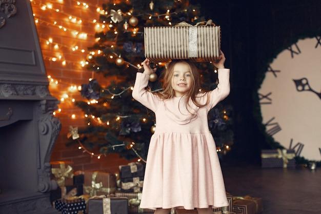 현재 크리스마스 트리 근처 귀여운 드레스 소녀