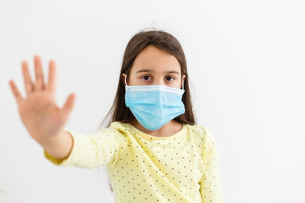 明るい背景の使い捨てマスクの少女。コロナウイルスのエピデミック保護