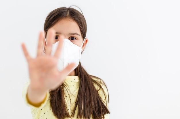 밝은 배경에 일회용 마스크를 쓴 어린 소녀. 코로나 바이러스 전염병 보호