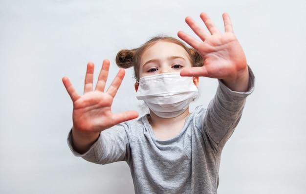使い捨てマスクの少女は彼女の手を示しています。コロナウイルスの流行防止