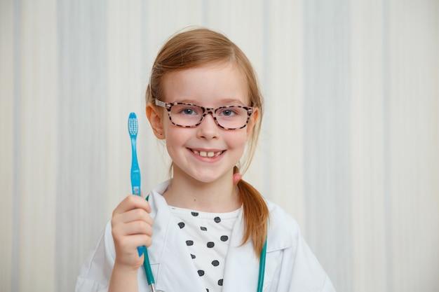 Маленькая девочка в халате доктора улыбается и показывает, что вам нужно почистить зубы.