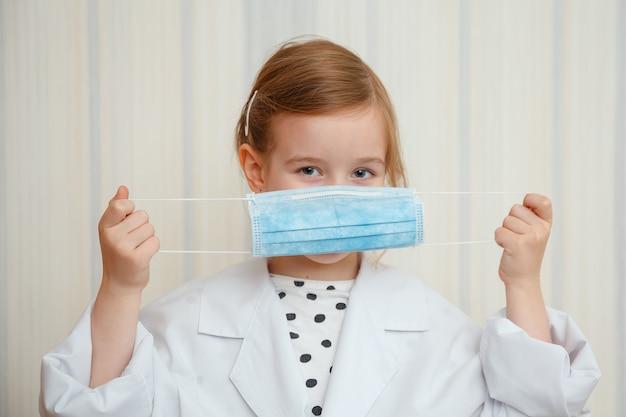 의사의 드레싱 가운과 마스크를 입은 어린 소녀는 모두가 보호 마스크를 착용해야한다는 제스처와 함께 보여줍니다.