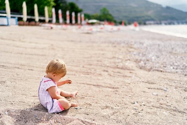 드레스를 입은 어린 소녀가 해변에서 모래를 가지고 노는 모습