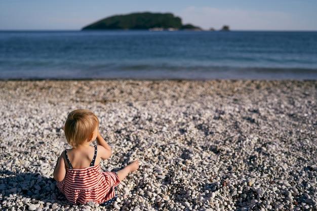 ドレスを着た少女が海の後ろの小石のビーチに座っています。
